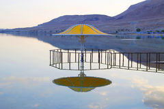 The gazebo for protection from the sun reflected in Dead Sea water at sunset Stock Images