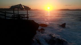 GAZEBO SILHOUETTE ON SUNSET WITH ROUGH SEA stock video footage