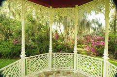 Gazebo in southern garden showing an Azalea garden surrounding it. Interior of a southern gazebo with white patterned woodwork shows the surrounding garden stock photos
