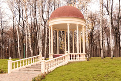 Gazebo surrounded by trees. Beautiful gazebo in a park surrounded by trees and grass Stock Photos