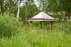 Gazebo in thickets of grass and bushes Stock Photo
