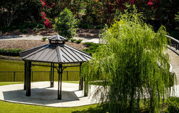 Gazebo and Weeping Willow Beside Pond. Gazebo and weeping willow tree beside pond with trees and flowers in the background and a bridge on the right Stock Photography