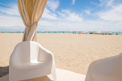 Gazebo with white chairs on the beach. Stock Photo