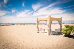 Gazebo with white chairs on the beach. Royalty Free Stock Photo