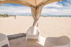 Gazebo with white chairs on the beach. Royalty Free Stock Image