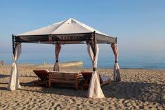 Gazeboen bäddar ned på sandsommarstranden, Grekland Fotografering för Bildbyråer