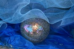 Gazing ball with netting and blue crete paper. Mosaic Gazing ball with netting and blue crete paper stock photo