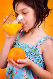 Gazing into the glass. A cute little dark haired girl drinking and gazing into a glass of fresh squeezed orange juice, holding an orange with orange background royalty free stock photography