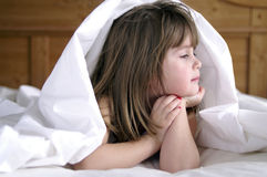 Gazing out the window. A young girl lying in the bed gazing out the window royalty free stock photo