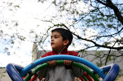 Gazing over... A young boy gazes over the swings in a park stock photos