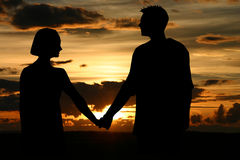 Gazing into sunset. A lovely couple gazing into sunset royalty free stock photo