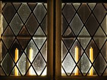 Backlit church window with candles inside. stock photography