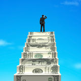 Gazing on top of money stairs. With blue sky background Stock Image