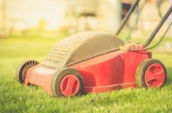 Gazonu kosiarz na trawie w jardzie przeciw światła słonecznego, gazonu kosiarzowi na trawie w jardzie przeciw światłu słonecznemu zdjęcie stock