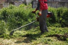 Gazonu kosiarza pracownika tnąca trawa w zieleni polu Zdjęcie Royalty Free
