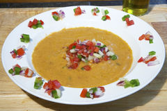 Gazpacho. Homemade gazpacho soup in a white bowl garnished with green pepper, tomatoe, cucumber and red onion and topped with olive oil Royalty Free Stock Photos
