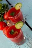 Gazpacho del tomate en vidrios sobre la tabla de madera azul Foto de archivo
