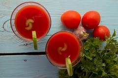 Gazpacho do tomate nos vidros sobre a tabela de madeira azul imagem de stock royalty free