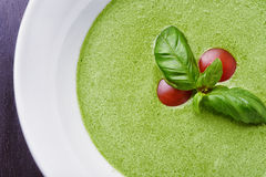 Gazpacho spinach with basil leaves and tomatoes. On desk Royalty Free Stock Photos