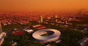 GBK football stadium at dusk time. Beautiful aerial view of Gelora Bung Karno football stadium with orange sky at dusk time in Jakarta, shot in 4k resolution stock video footage