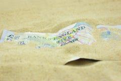 GBP σημείωση πέντε λιβρών που καλύπτεται στην άμμο Στοκ Εικόνα