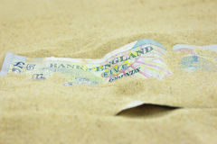 GBP Five Pound note covered in sand Stock Image