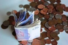 GBP tjugo pund pengarrulle och mynt är liyng på en tabell arkivbild