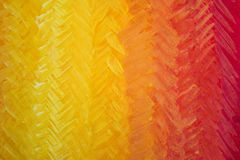 Gdaddientny background with visible brush strokes. Brush strokes form herringbone pattern. A beautiful smooth transition from red to yellow and back stock photo