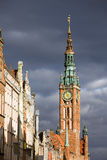 Gdansk Old Town. Town Hall (Polish: Ratusz Glownego Miasta) clock tower in the Old Town of Gdansk (Danzig) in Poland, bathed in sunlight, just before the storm Royalty Free Stock Photography