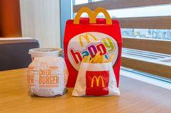 Mcdonalds happy meal box with Coca-Cola, french fries and cheeseburger on wooden table. Royalty Free Stock Images