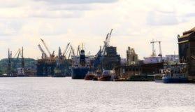 Gdansk, Polonia - 21 de junio de 2016: muchas grúas en fondo, trabajadores, barco de envío Imágenes de archivo libres de regalías