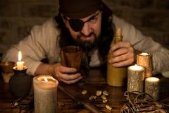 Gderliwy pirat z butelką rumowy obsiadanie na średniowiecznym stole obraz royalty free