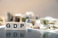 GDP Word Written In Wooden Cube reflection on black mirrow with stock image