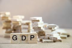 GDP Word Written In Wooden Cube on wood table with wooden stack stock photos
