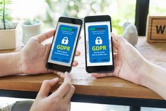 GDPR concept. Data protection laws and regulation or cyber security and privacy. Close up two asian hands using smart phone to accept User`s agreement of new stock image