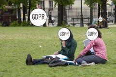 GDPR - duas meninas estão sentando-se na grama no parque, suas caras são escondidas pela proteção de dados geral da inscrição fotografia de stock royalty free
