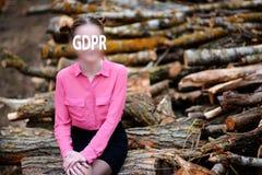 Gdpr härlig ung kvinna som sitter på bunten av avverkade trädstammar i skogen arkivbilder