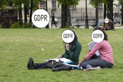 GDPR - two girls are sitting on the grass in the park, their faces are hidden by the inscription General Data Protection royalty free stock photography