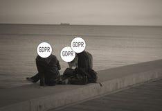 GDPR - um par novo com um cão que fala na praia, suas caras é escondido atrás da proteção de dados geral da inscrição fotos de stock royalty free