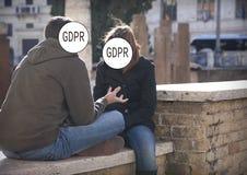 GDPR - um par novo tem uma conversação tensa, suas caras é escondido pelo regulamento geral da proteção de dados da inscrição fotografia de stock royalty free