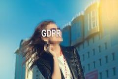 GDPR - vrouw die haar gezicht met een inschrijving GDPR verbergen stock foto