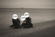 GDPR - a young couple with a dog talking on the beach, their faces are hidden behind the inscription General Data Protection royalty free stock photos