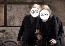 GDPR - zwei ältere Menschen, sprechend, die Straße unten gehend ihre Gesichter werden mit dem Schutz Aufschrift General-Daten bed lizenzfreie stockfotos