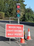 Gdy czerwonych świateł przedstawienia czekają tutaj szyldowego i światła ruchu obraz stock