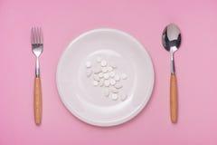 gdy zdrowy posiłek pigułki słuzyć Lek kapsuła na bielu talerzu na p Obrazy Royalty Free