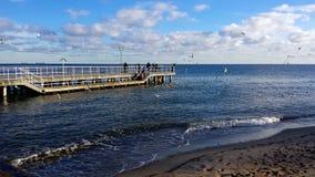 Sunday walk by the sea. Gdynia, Poland - January 07, 2018: Sunday walk by the sea, people feed birds Stock Images