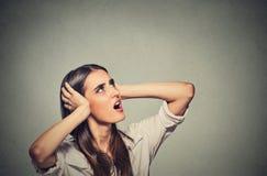 Geërgerde beklemtoonde vrouw die haar oren behandelen, die omhoog boven hevig lawaai kijken royalty-vrije stock fotografie
