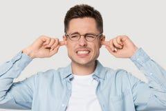 Geërgerde mens die in de oren van de glazendekking luid geluid vermijden stock foto