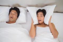 Geërgerde vrouw die haar oren behandelen met hoofdkussens om het snurken te blokkeren Stock Foto's