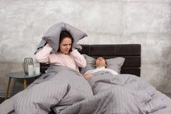 Geërgerde vrouw die haar oren blokkeren door een hoofdkussen van lawaai van echtgenoot stock afbeeldingen